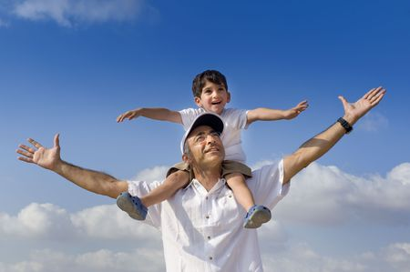 son riding on his father shoulders with spread arms の写真素材