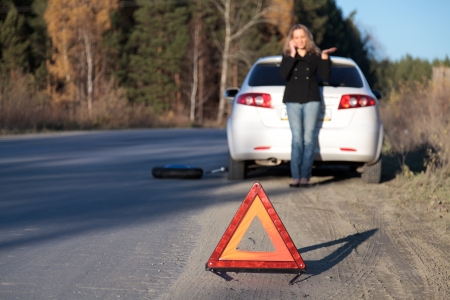 Young woman standing by her damaged car and calling for help. Focus is on the red triangle sign. Shallow depth of view