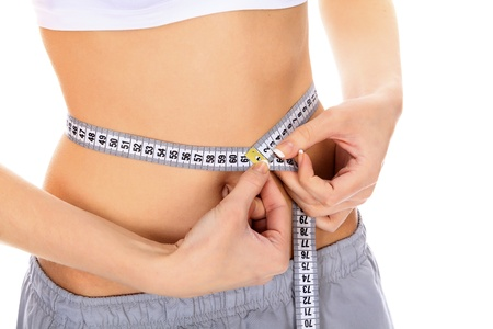 Cropped image of a fit young woman measuring her waistline