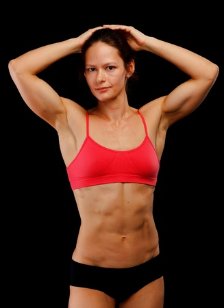 Female athlete posing against black background