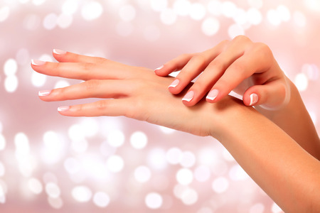 Photo for Beautiful woman hands against an abstract background with blurred lights - Royalty Free Image