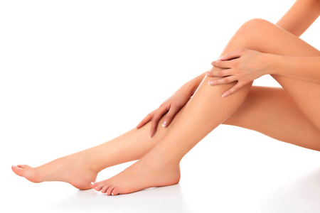 Photo pour Closeup shot of beautiful female legs and hands. Woman touches her smooth skin with french manicured hands. Isolated on white background - image libre de droit