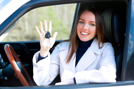 Photo pour Happy woman driver with car keys sitting in white car with open window - image libre de droit