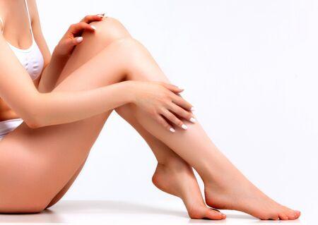 Foto de Wellness and beauty concept, beautiful slim woman in white underwear sitting on white floor - Imagen libre de derechos