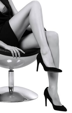 Photo pour Woman with long legs sitting in a chair, isolated on white background - image libre de droit