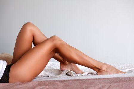 Photo pour Tanned female legs on a bed - image libre de droit