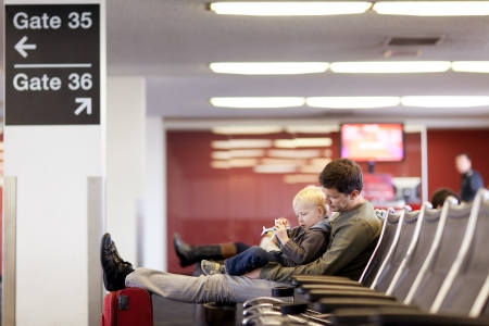 father and his son waiting and playing at the airport