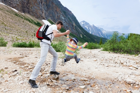 father helping his son to jump over stream in jasper national park