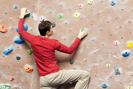 young caucasian man rock climbing indoors