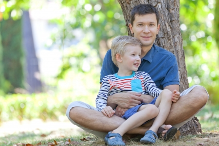 handsome smiling father and his cute son sitting together in the woods