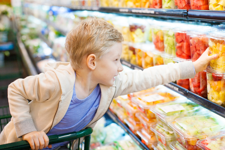 positive 6-year old boy buying healthy fruits at supermarket or grocery store helping his parents