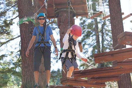 positive little boy and his father climbing at outdoor treetop adventure park being active and healthy together