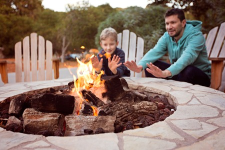 Photo for view of firepit and happy smiling family of two, father and son, warming their hands by the fire and enjoying time together in the background - Royalty Free Image