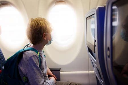 Photo pour boy wearing face mask sitting in airplane cabin, travel during coronavirus pandemic concept - image libre de droit