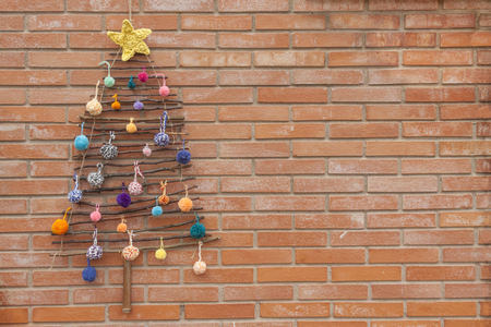 a horizontal frontal view of some handmade xmas decorations: a tree decorated with pompom over a brick wall with a space for a message