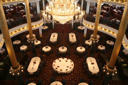 Photo pour A huge chandalier hangs over tables in an elegant dining room - image libre de droit