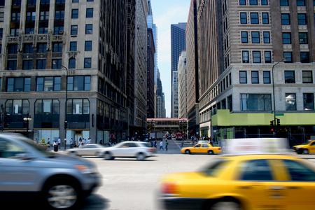 Cars race by on a busy city street