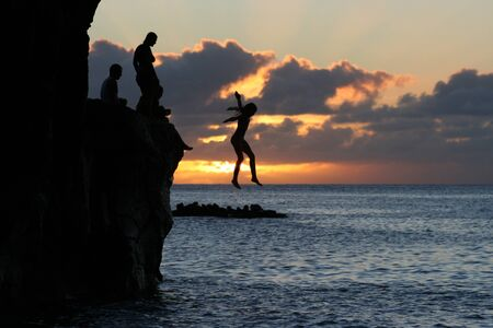 Girl jump off a cliff into the ocean at Waimea Bay in Hawaii at sunset.