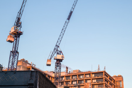Photo pour Two cranes in a construction site just behind one of the biggest hospitals in London - image libre de droit