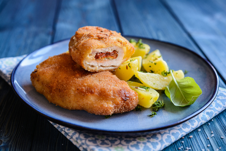 Fried breaded pork cutlets stuffed with sun - dried tomato and Roquefort cheese, served with boiled potato