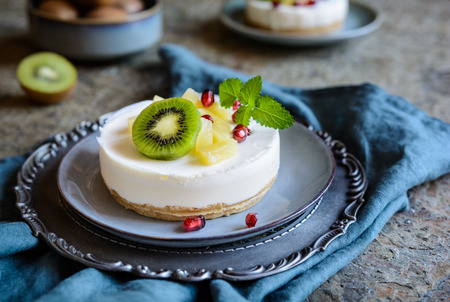 Delicious unbaked mini cheesecakes topped with pineapple, kiwi and pomegranate
