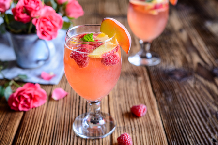 Foto de Refreshing raspberry peach mimosa drink on a wooden background - Imagen libre de derechos