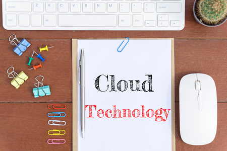 Text Cloud technology on white paper which has keyboard mouse pen and office equipment on wood background / business concept.