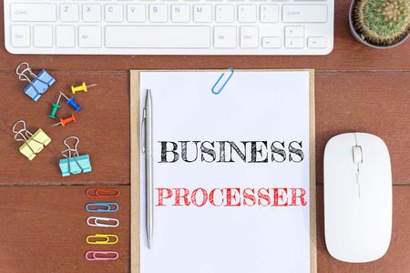 Text Business processor on white paper which has keyboard mouse pen and office equipment on wood background / business concept.