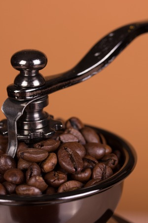 Vintage manual coffee grinder on a brown background