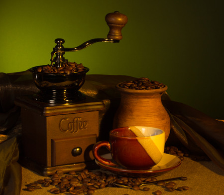 Vintage coffee grinder, cup with a drink and a pitcher with roasted beans