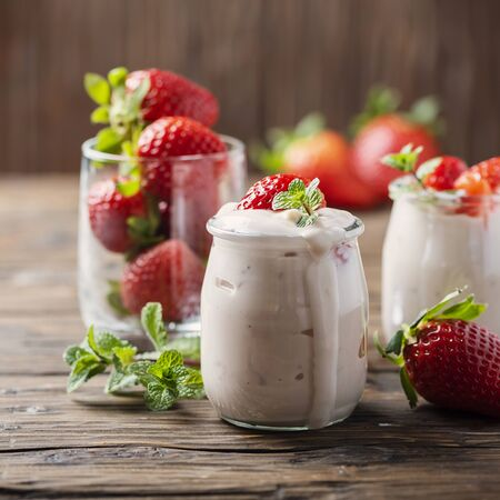 Photo for Healthy yougurt with stawberry and mint on the wooden table, selective focus and square image - Royalty Free Image