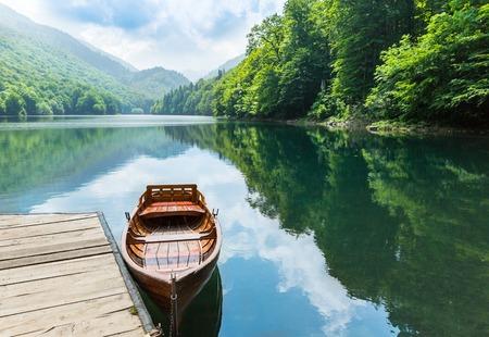 Wooden boat at pier on mountain lake. Biograd lake, Montenegro