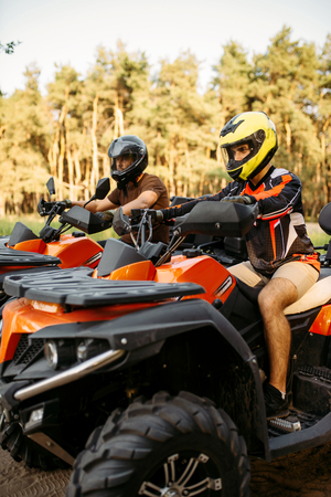 Photo pour Two atv riders before the trip in summer forest - image libre de droit