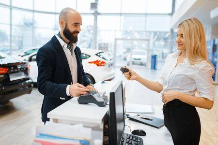 Photo pour Female seller gives keys to man in car dealership - image libre de droit