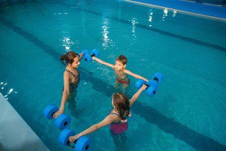 Photo pour Children swimming group, workout with dumbbells - image libre de droit