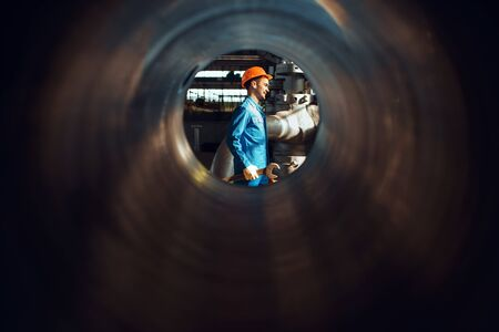 Photo pour Worker with wrench on factory, view through tube - image libre de droit