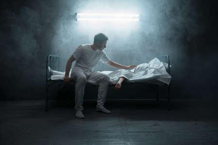 Photo pour Sad psycho man looking on dead woman in bed - image libre de droit