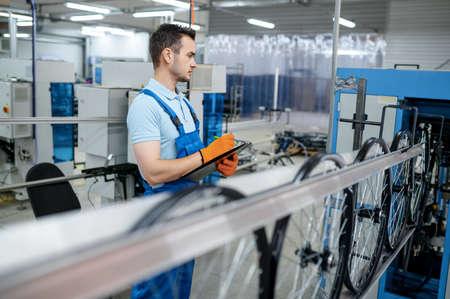 Photo pour Worker at the machine tool makes bicycle rim - image libre de droit
