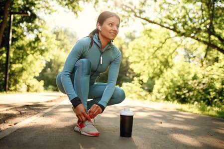 Photo pour Workout in park, smiling woman in headphones - image libre de droit