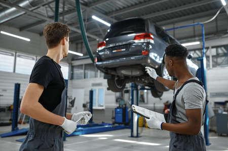 Photo pour Two male mechanics talking in car service - image libre de droit