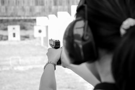 A women shooting a 9 m.m pistal in BW colour tone.