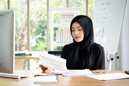 Photo pour Portrait of smart beautiful Asian Muslim businesswoman working in the office, Diversity cultural and gender concept. - image libre de droit