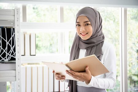 Photo for Asian Muslim businesswoman choosing a books on book shelf in her office, Muslim woman student. - Royalty Free Image