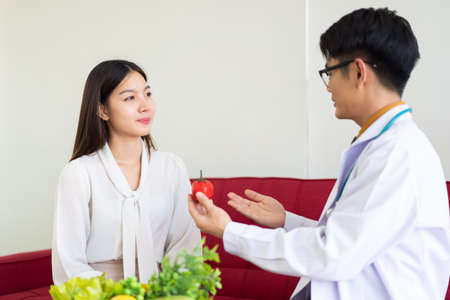 Photo pour Asian young woman having a consultation with expert and professional nutritionist in hospital for planning about nutrition and eating program. Beautiful girl consult with doctor for food nutrition. - image libre de droit