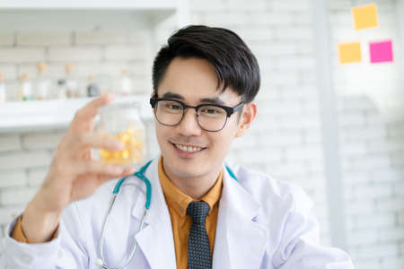 Photo pour Happy Asian nutritionist doctor showing up a vitamin or nourishment capsules in a bottle close up. Doctor smiling to camera and presenting a vitamin supplement. - image libre de droit