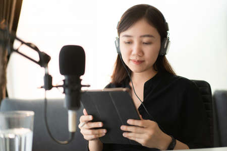 Foto de Happy Asian woman setting up a living room in her house for podcast studio, woman arranging a podcast and online radio station at home. Professional young podcaster speaking through a microphone. - Imagen libre de derechos