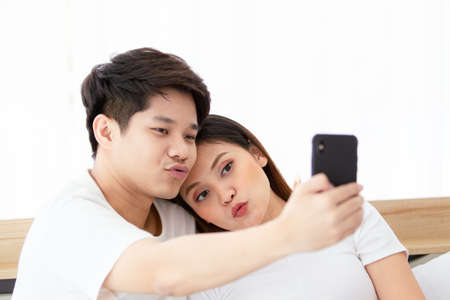 Foto de Happy Asian young couple enjoy taking a selfie photography on the bed in bedroom, cheerful Asian husband and wife living together in bedroom. Couple using smartphone to take a selfie photo. - Imagen libre de derechos