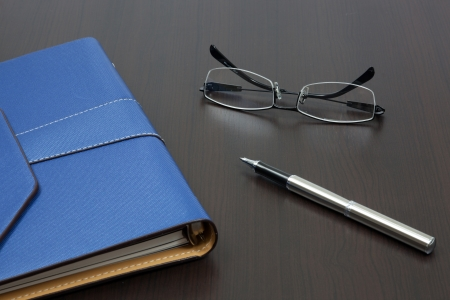 Organizer on table with pen and glasses