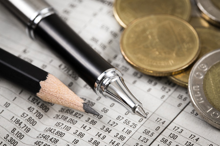 Business diagram on financial report with coins. Accounting