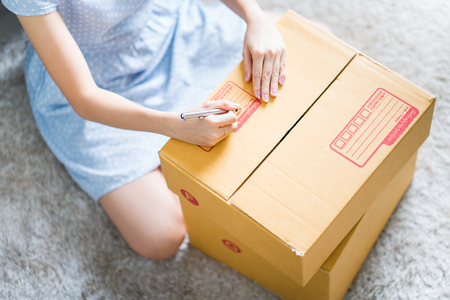 Woman signs papers among parcels. Delivery concept